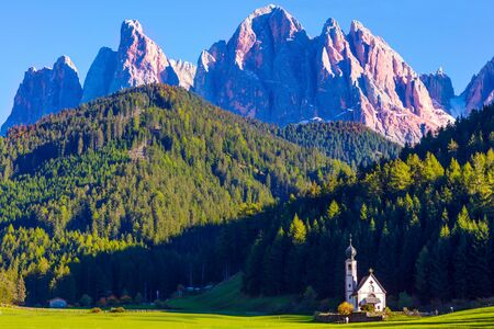 The gorgeous village Santa Maddalena in the Val di Funes Valley. Tyrol, Italy. Small white church with a bell among green lawns on the sunset. The concept of ecological and photo tourism