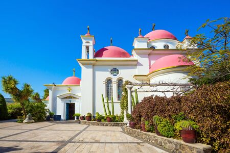 Capernaum, Lake Tiberias. Place of worship and pilgrimage. Snow-white church building with pink domes and golden crosses. Israel. The concept of religious pilgrimage and photo tourism Standard-Bild