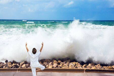 Winter storm in the Mediterranean Sea. Woman performs asana yoga. High foamy surf on Tel Aviv embankment. Concept of eco, active and photo tourism