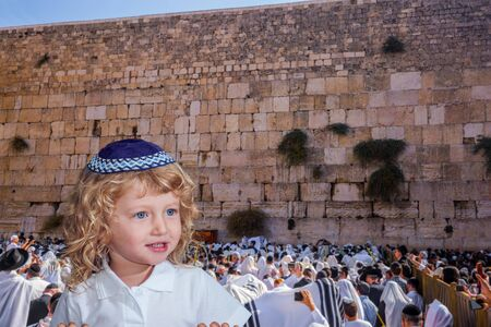 Charming little Jewish blond boy with blue eyes in a yarmulke. The blessing of the Cohen. Ceremony at the Temple Mount in Jerusalem. Jews praying at the Western Wall. The concept of religious and photo tourism
