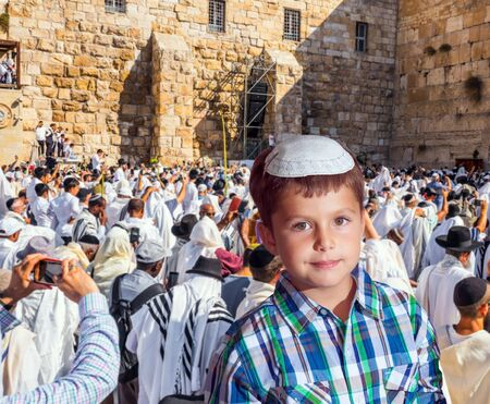 Handsome Jewish boy in yarmulke. Jews praying at the Western Wall. The blessing of the Cohen. Solemn ceremony at the Western slope of the Temple Mount in Jerusalem. The concept of religious and photo tourism