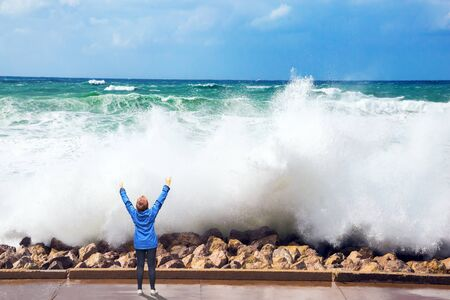 Winter storm in the Mediterranean Sea. High foamy surf on Tel Aviv embankment. Woman in blue jacket admired by raging sea and high waves. Concept of eco, active and photo tourism Imagens