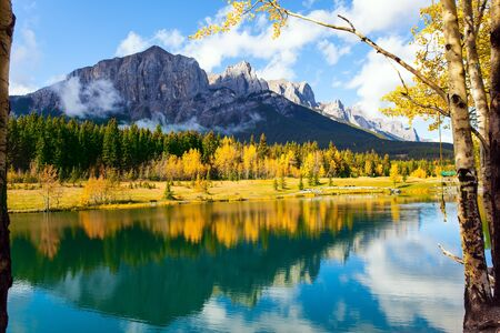 Lush autumn in the Canadian Rockies. Bright autumn forest is reflected in the smooth water of the lake. Outskirts of Canmore. The concept of active, ecological and photo tourism