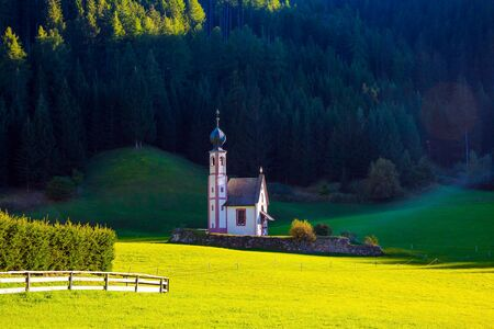 Tyrol, Italy. The Val di Funes Valley. Majestic Dolomites. Small white church with a bell among green lawns on the sunset. The concept of active, ecological and photo tourism Foto de archivo