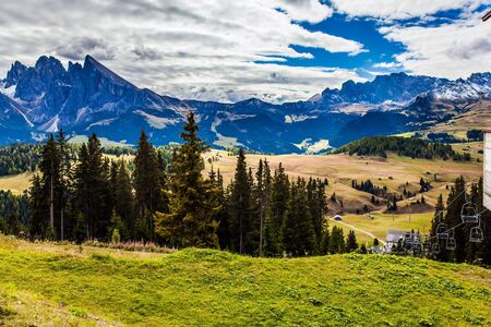 The Dolomites, Italy. Magnificent rocky ridge borders a hilly valley Alpe di Siusi. Picturesque grassy hills. Sunny day for photographing and hiking. The concept of walking, ecological and photo tourism