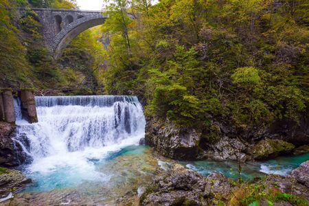 Slovenia. Picturesque old bridge over the Vintgar mountain gorge. Powerful rumbling waterfall on a mountain river. The concept of active and photo tourism 写真素材