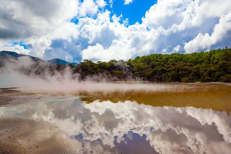 Cumulus clouds are picturesquely reflected in the smooth surface of hot water. New Zealand, North Island. Wai-O-Tapu Geyser Park. The concept of exotic, ecological and photo tourism