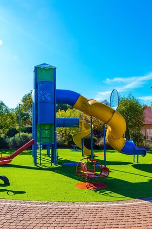 Open sun lawn for kids. Morning. Various multi-colored attractions. Cozy and safe children 's playground. Concept of physical and mental development of children