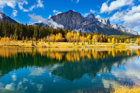 The Canadian Rockies. The city of Canmore in Banff Park. Bright autumn forest is reflected in the smooth water of the lake. The concept of active, ecological and photo tourism 版權商用圖片