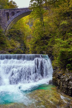 Slovenia. Picturesque old bridge over the Vintgar mountain gorge. The concept of active and photo tourism. Powerful rumbling waterfall on a mountain river