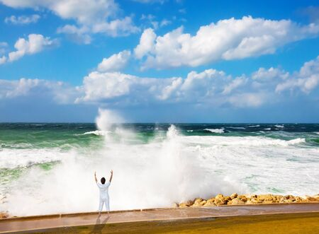 High foamy surf on Tel Aviv embankment. Winter storm in the Mediterranean Sea. Woman performs asana yoga. Concept of eco, active and photo tourism Imagens