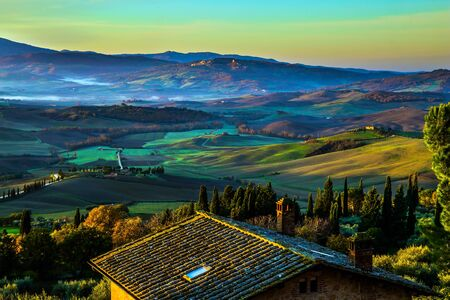 Predawn dusk. The sky is turning pink over the hills. Picturesque valley in central Italy. Tuscany. Photo taken on a protective wall around the ancient city of Pienza