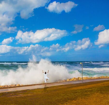 Winter storm in the Mediterranean Sea. High foamy surf on Tel Aviv embankment. Woman performs asana yoga. Concept of eco, active and photo tourism