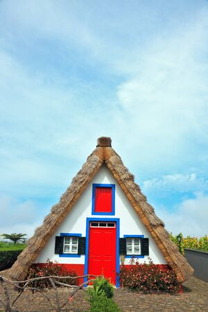 A house with a thatched gable roof. Adorn the facade of the red door and red top window. Stockfoto
