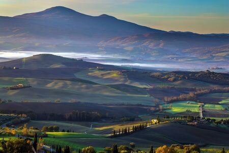 Picturesque valley in central Italy. Tuscany. Predawn dusk. The sky is turning pink over the hills. Photo taken on a protective wall around the ancient city of Pienza