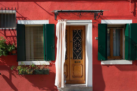 Province of Veneto. Burano is an island of colorful bright houses and the finest lace near Venice. The windows is decorated with flowers. The concept of cultural, historical and photo tourism