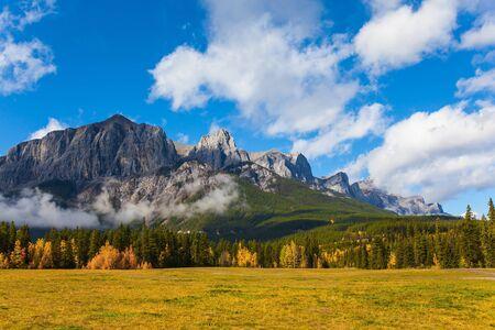 カナダのロッキー山脈の緑豊かな明るい秋の日。雄大なロッキー山脈。三姉妹山は青々とした白い雲で覆われています。アクティブ、エコ、フォトツーリズムのコンセプト