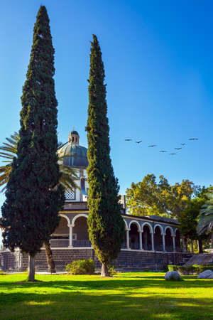 The Catholic Church of the Italian female Franciscan monastery on Mount Bliss in the Galilee. Flock of migratory birds flies. High shore of Lake Tiberias. The concept of religious pilgrimage and photo tourism Standard-Bild