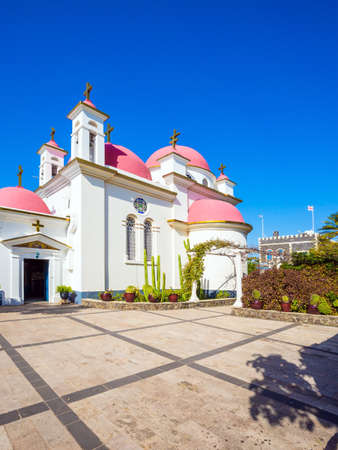 Israel, Capernaum, Lake Tiberias. Place of worship and pilgrimage. Snow-white church building with pink domes and golden crosses. The concept of religious pilgrimage and photo tourism