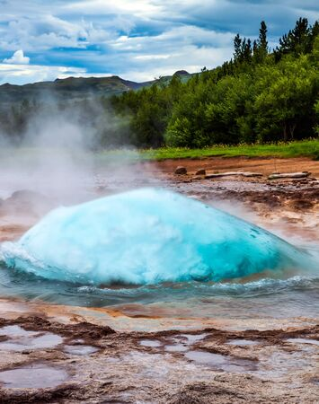 Boiling water azure ball. The famous Strokkur geyser. Cloudy summer cold day. Volcanic steaming hot field. Travel to Iceland. The concept of active, ecological and exotic travel