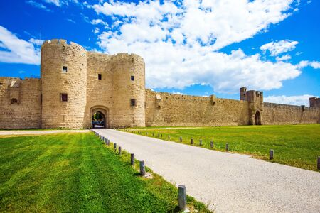 Picturesque powerful gates and fortifications defend the port city of Aigues-Mortes. The concept of historical and photo tourism. Around the walls are green lawns