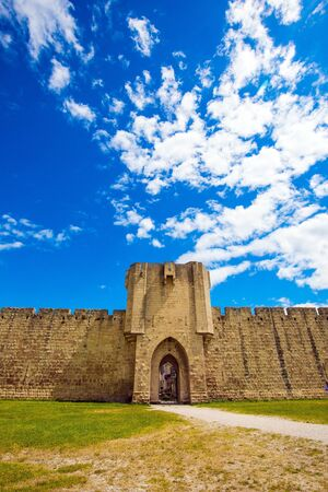 Picturesque powerful gates and fortifications defend the port city of Aigues-Mortes. Journey to History. Southern France. Around the walls are green lawns
