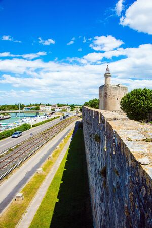 Antique walls of the medieval port city of Aigues-Mortes. Shipping channel flows into the Mediterranean Sea. France. The concept of historical and photo tourism