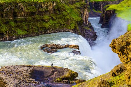 Iceland. Tourist with a photo bag takes pictures of a bubbling waterfall. Gullfoss