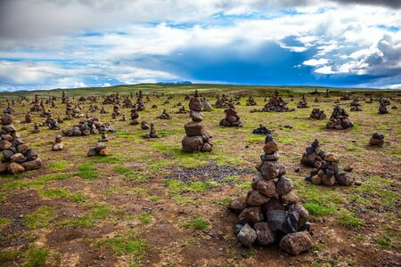Field of stone pyramids. Stone pyramids bring good luck in the journey. The stone pyramids are a symbol of Iceland. Cloudy summer cold day. The concept of active, ecological and exotic travel