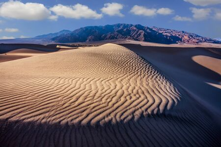 Mesquite Flat Sand Dunes - dunes in Death Valley. USA, California. Morning light illuminates the soft sandy hills. The sand lies in light waves. The concept of active, extreme and photo tourism Reklamní fotografie