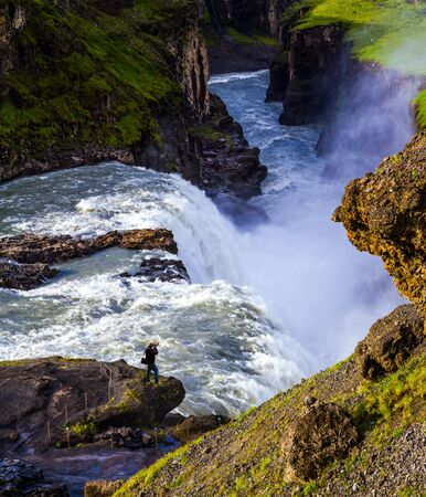 """Iceland. Gullfoss """"Golden Falls"""" - the waterfall fed by glacial water. Tourist - photographer with photo bag takes pictures of burrowing waterfall. The concept of extreme and photo tourism"""