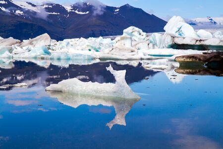 The lagoon Jokulsaurloun. Iceland. Bizarre icebergs and floating ice floes reflected in the smooth cold water of the lagoon. Cold summer day. The concept of northern and photo tourism