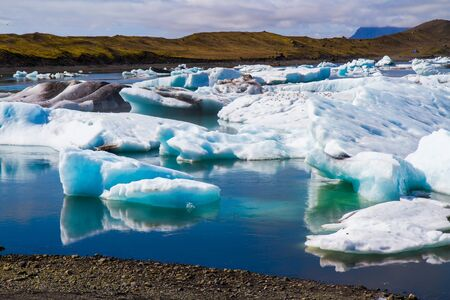 Iceland. The lagoon Jokulsaurloun in Skaftafell Park. Cold day in July. White and blue icebergs and ice floes reflected in the water. The concept of extreme, northern and photo tourism 写真素材