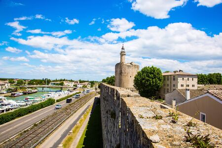 Shipping channel flows into the Mediterranean Sea. France. Antique walls of the medieval port city of Aigues-Mortes. The concept of historical and photo tourism