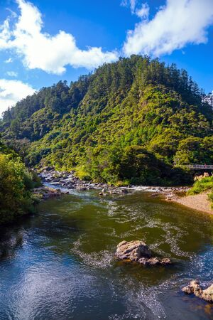 Travel to New Zealand, North Island. Karangahake Gorge. The river flows among abandoned gold mines. The blue sky is reflected in the water. The concept of active, exotic and photo tourism
