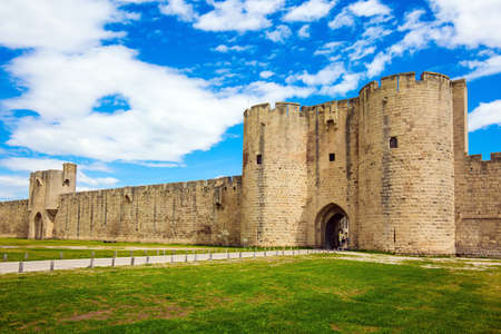 Southern France. Journey to History. Picturesque powerful gates and fortifications defend the port city of Aigues-Mortes. Around the walls are green lawns