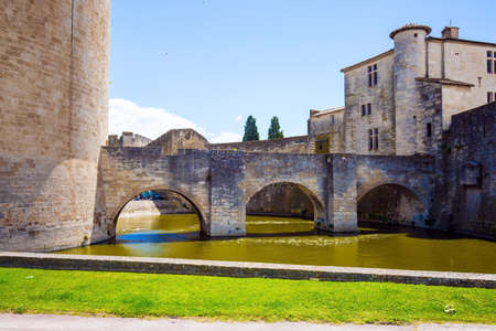 Powerful medieval walls and a moat with water surround the ancient city of Aigues-Mortes. Mediterranean coast of France. The concept of active, historical and photo tourism 写真素材