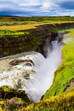 """Southwest Iceland. The rumbling waterfall is fed by thawed glacial water. The concept of extreme and photo tourism. Gullfoss """"Golden Falls"""" - the beautiful waterfall in Iceland, on the Hvita River"""