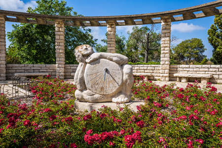 Sundial is carved in stone. Observation deck overlooking the Mediterranean Sea. Blooming rose garden. Magnificent park on the slopes of Mount Carmel in Israel