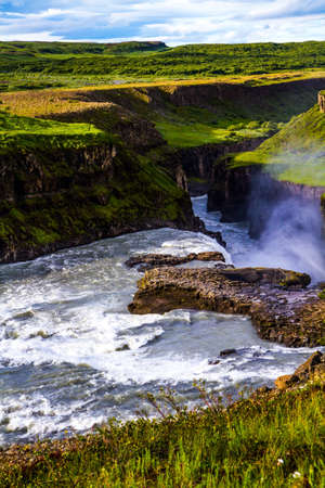 """Gullfoss """"Golden Falls"""" - the waterfall in Iceland, on the Hvita River. Southwest Iceland. The rumbling waterfall is fed by thawed glacial water. The concept of extreme and photo tourism"""