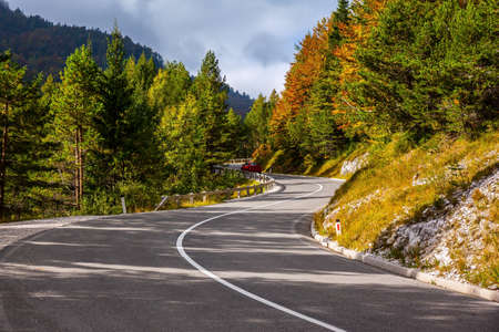 Golden Autumn in Slovenia. Magnificent Julian Alps, mountain range, spur of the Alps. Sunset, a big cloud is approaching. Asphalt road in the mountains