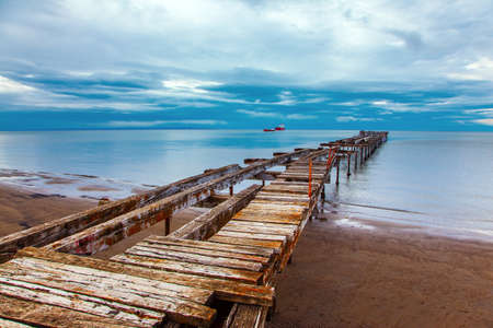 South America. Strait of Magellan. Ruined ocean pier in Punta Arenas. The wooden dock flooring collapsed and rotted. The famous Tierra del Fuego is visible on the horizon. Stock Photo