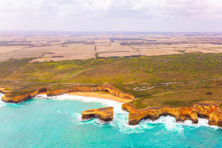 "Helicopter flight over the scenic Pacific coastline. Cloudy day. Legendary cliffs ""Twelve Apostles"" in the snow-white foam of the ocean surf. Great Ocean Road. Bird's eye view. Australia"