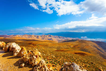 Sunset sunbeams illuminate scenic hills. Ancient terracotta-colored mountains surround the healing waters of the Dead Sea. Legendary Dead Sea. Israel