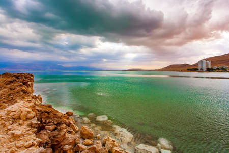 Ancient terracotta-colored mountains surround the healing waters of the Dead Sea. Low winter clouds are reflected in the green sea water. Israel. The picturesque Dead Sea