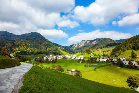 Small village in mountain valley. Travel to Slovenia. Picturesque Julian Alps. Beautiful autumn day. Charming pastoral. Green grassy lawns in a mountain valley.