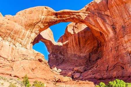 Double Arch. The beauty of Arches Park in USA. Picturesque red-brown sandstone cliffs form a unique landscape. Grandiose rock compositions natural origin. Stock Photo