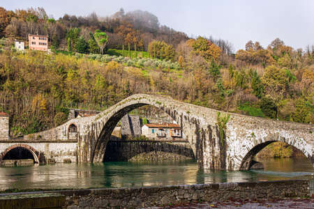 Picturesque stone bridge of magnificent architecture built a thousand years ago. Devil's Bridge over the Sercchio River. Cold windy winter day. Travel to fabulous Italy
