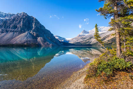 Glacial lake Bow with clear azure water. Mountains are reflected in the smooth water of the lake. Sunny autumn day. Rocky Mountains, Canada.