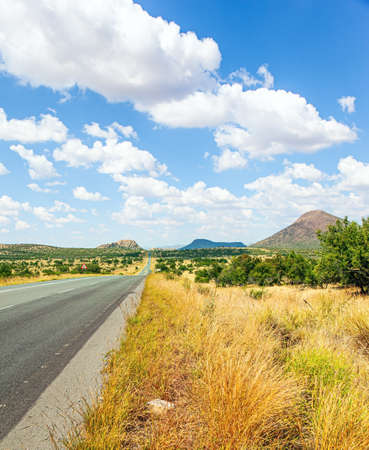 Paved highway crosses flat savannah. Travel to Africa. The magical desert in Namibia. Hot day, lush clouds float in the blue sky.